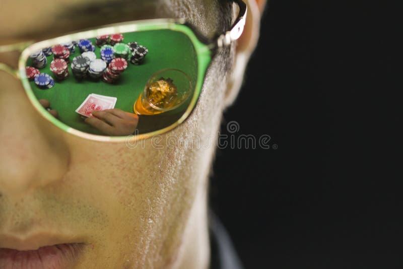 Sirva jugar el póker con la reflexión a través de sus gafas de sol foto de archivo
