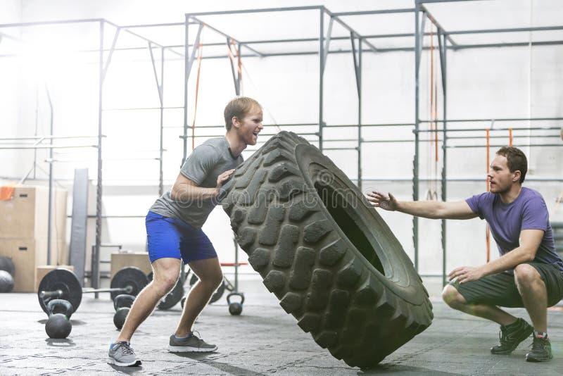 Sirva la ayuda en el amigo dedicado en mover de un tirón el neumático en el gimnasio del crossfit fotos de archivo