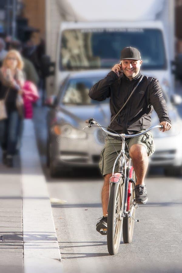 Sirva la bicicleta del montar a caballo y hablar en el teléfono foto de archivo libre de regalías