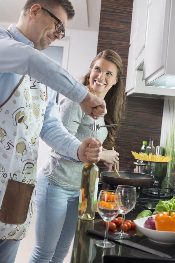Sirva la botella de vino de la abertura mientras que cocina con la mujer en cocina fotos de archivo