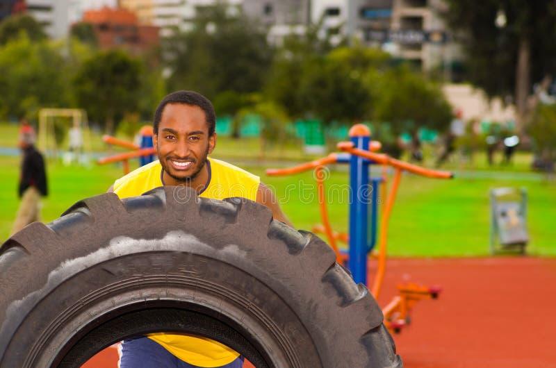 Sirva la camisa amarilla que lleva y los pantalones cortos azules que levantan el neumático grande del tractor durante el ejercic foto de archivo libre de regalías