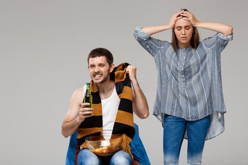 Sirva la cerveza de consumición, fútbol de observación, mujer trastornada que se coloca detrás imagen de archivo libre de regalías