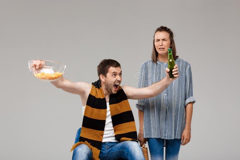 Sirva la cerveza de consumición, fútbol de observación, mujer trastornada que se coloca detrás, llorando fotos de archivo