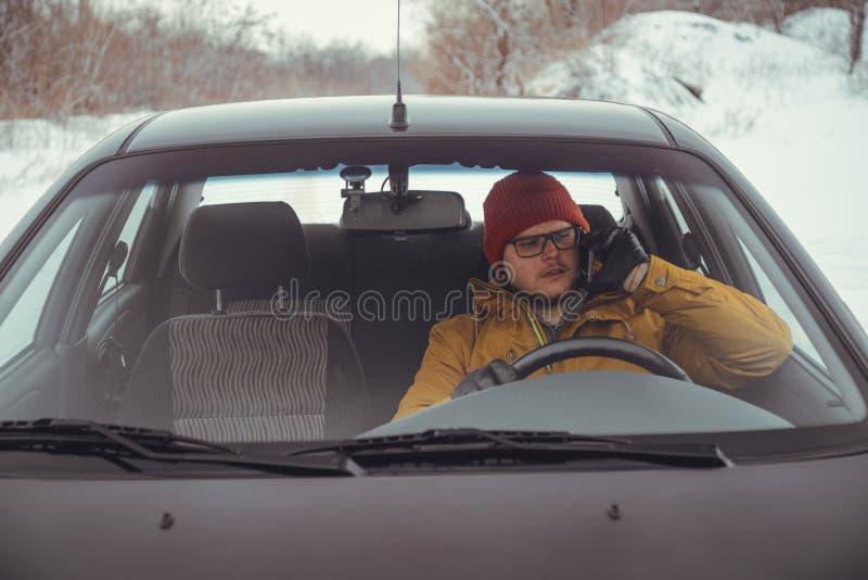 Sirva la conducción del coche usando el teléfono elegante en coche fotos de archivo
