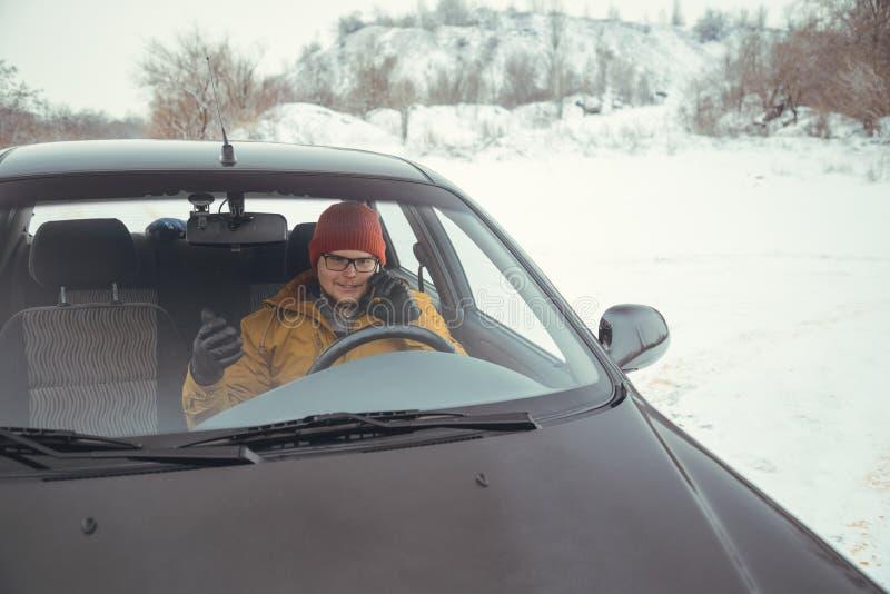 Sirva la conducción del coche usando el teléfono elegante en coche fotos de archivo libres de regalías