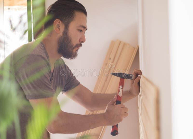 Sirva la construcción de una casa y de un workimg con el martillo y la madera fotografía de archivo libre de regalías