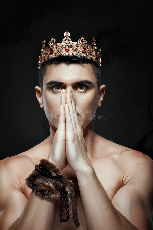 Sirva la corona en su cabeza para rogar con las manos dobladas imagenes de archivo