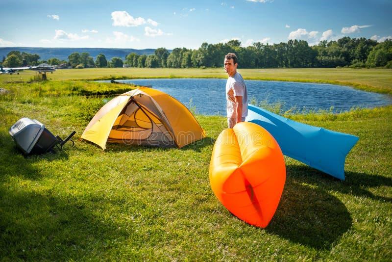 Sirva la determinación de los sofás inflables hacia fuera en acampar salvaje imagen de archivo libre de regalías