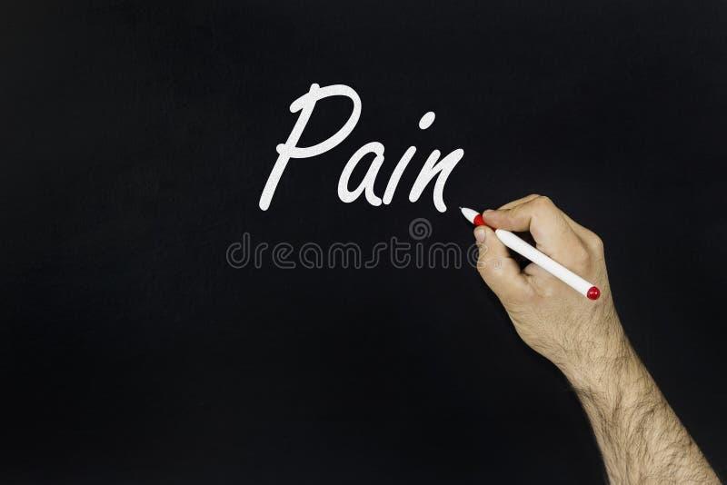 Sirva la escritura del dolor de la palabra en una pizarra imagen de archivo libre de regalías