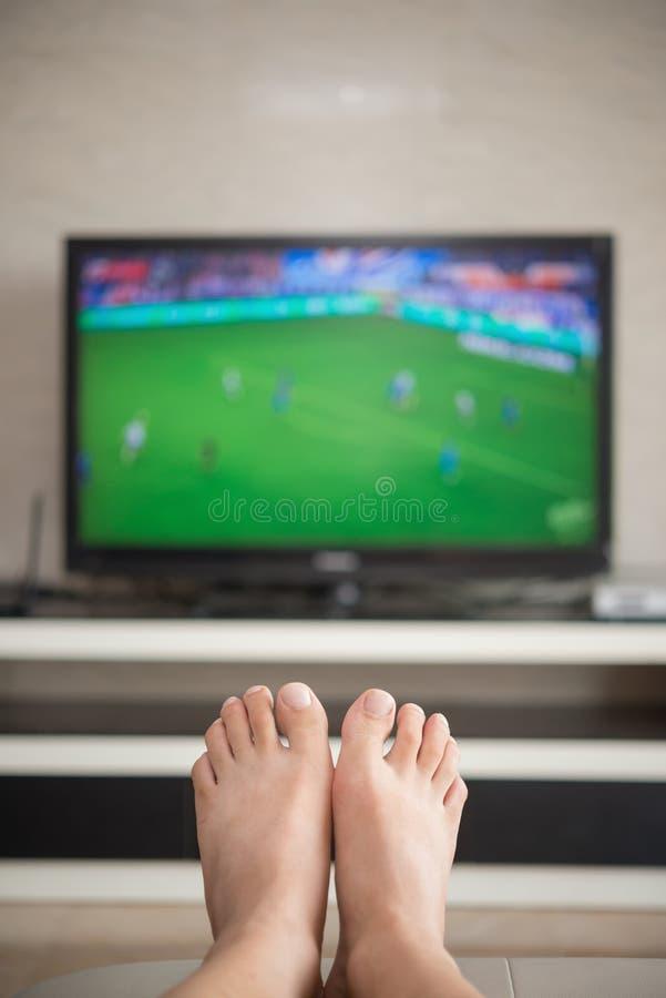 Sirva la fijación en un sofá en casa que mira el partido de fútbol imágenes de archivo libres de regalías