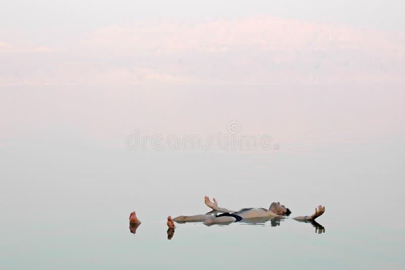Sirva la flotación en un agua vidriosa del mar muerto fotografía de archivo