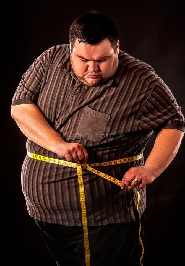 Sirva la grasa del vientre con pérdida de peso de la cinta métrica alrededor de cuerpo fotografía de archivo libre de regalías