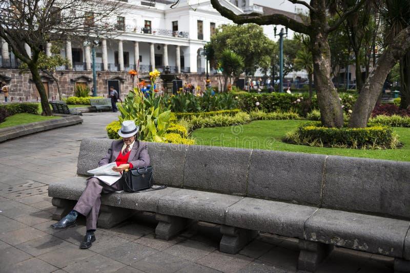 Sirva la lectura de un periódico en un banco en un parque en el cuadrado de la independencia en la ciudad de Quito, en Ecuador foto de archivo libre de regalías