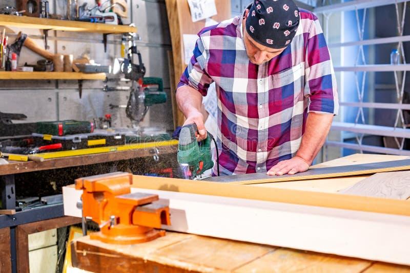 Sirva la madera del sawing con una segueta en un banco de trabajo imagenes de archivo