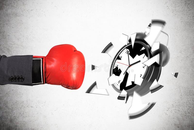 Sirva la mano del ` s en el guante de boxeo que rompe el despertador fotografía de archivo libre de regalías