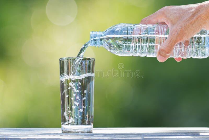 Sirva la mano del ` s que sostiene el agua de botella plástica y que vierte el agua en el vidrio en la tabla de madera en fondo v imagen de archivo libre de regalías