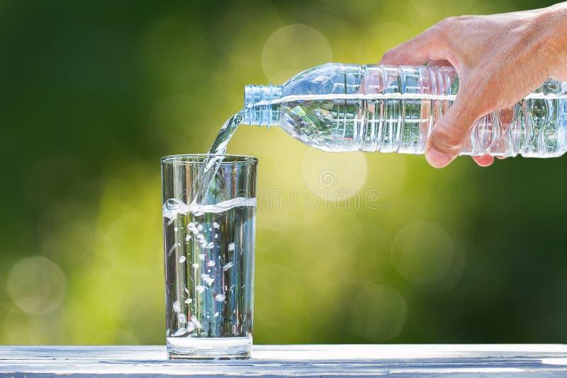 Sirva la mano del ` s que sostiene el agua de botella plástica y que vierte el agua en el vidrio en la tabla de madera en fondo v fotografía de archivo libre de regalías