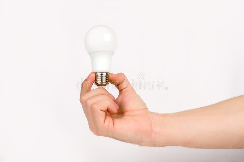 Sirva la mano del ` s que sostiene la lámpara del LED imágenes de archivo libres de regalías