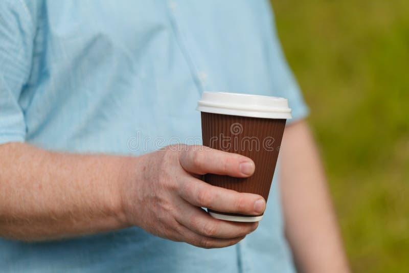 Sirva la mano del ` s que sostiene la taza de café de papel Bebida en la calle imágenes de archivo libres de regalías