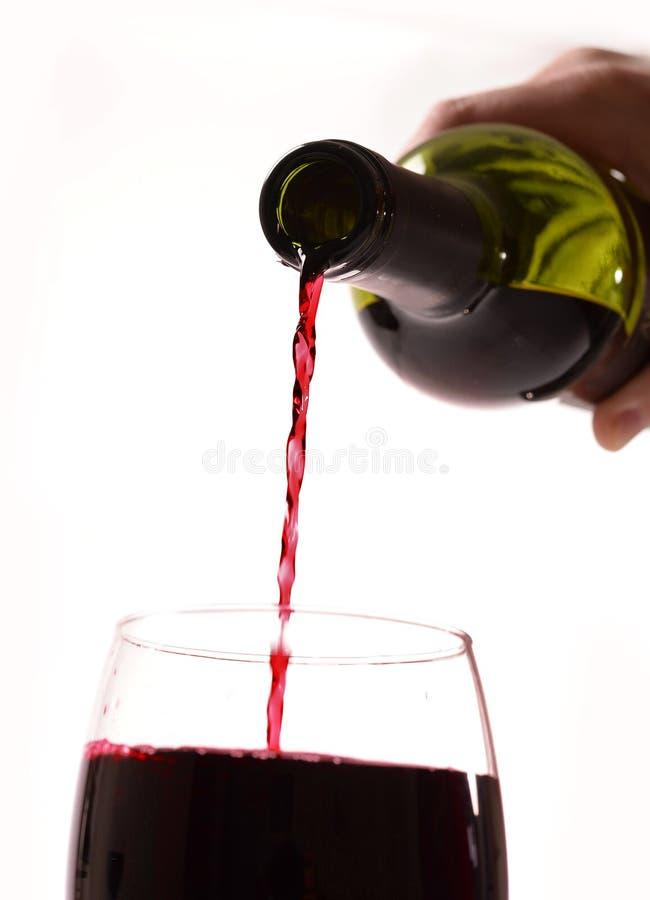 Sirva la mano que celebra embotellado de cristal con el vino rojo imagenes de archivo