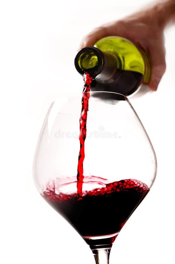 Sirva la mano que celebra embotellado de cristal con el vino rojo foto de archivo