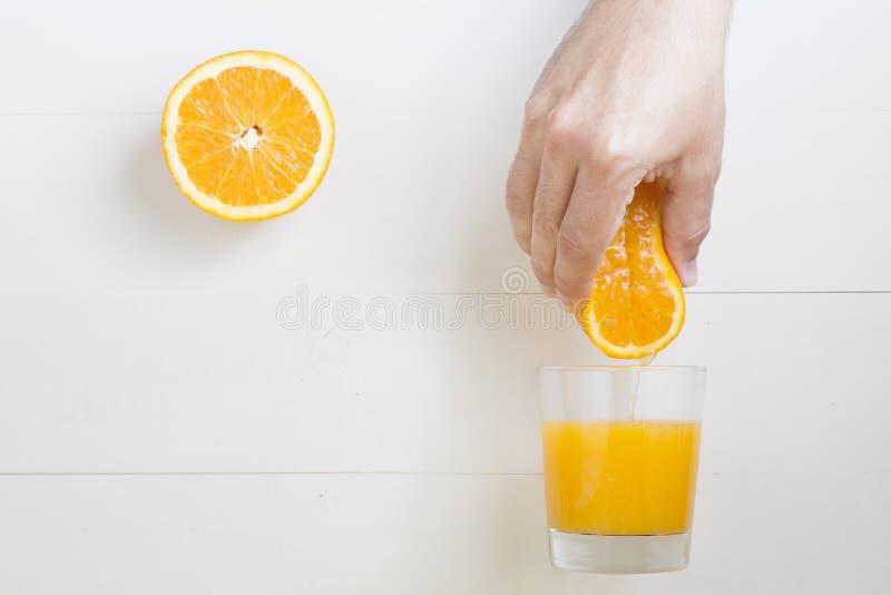 Sirva la mano que exprime la naranja sobre el vidrio del zumo de naranja fotografía de archivo libre de regalías