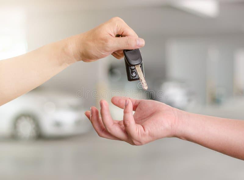 Sirva la mano que lleva a cabo una llave del coche y que la entrega a otra persona fotografía de archivo