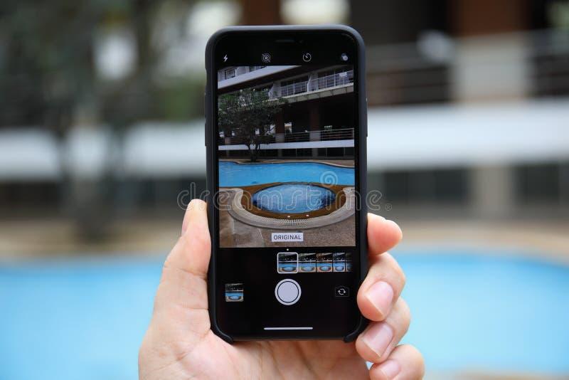 Sirva la mano que sostiene el iPhone X con la cámara de la foto en la pantalla fotografía de archivo libre de regalías