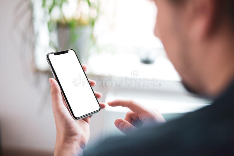 Sirva la mano que sostiene el smartphone negro con la pantalla en blanco grande y el marco moderno menos dise?o fotografía de archivo libre de regalías