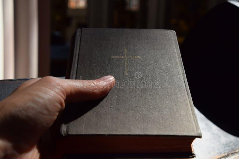 Sirva la mano que sostiene la biblia en iglesia sobre el banco de madera imagenes de archivo