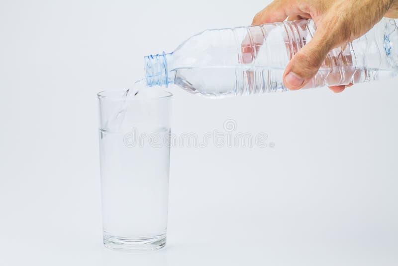 Sirva la mano que sostiene la botella de agua plástica y poring el agua en el vidrio fotos de archivo
