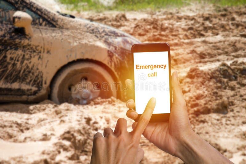 Sirva la mano usando el smartphone que llama la emergencia para el st del neumático de coche de la ayuda imagen de archivo