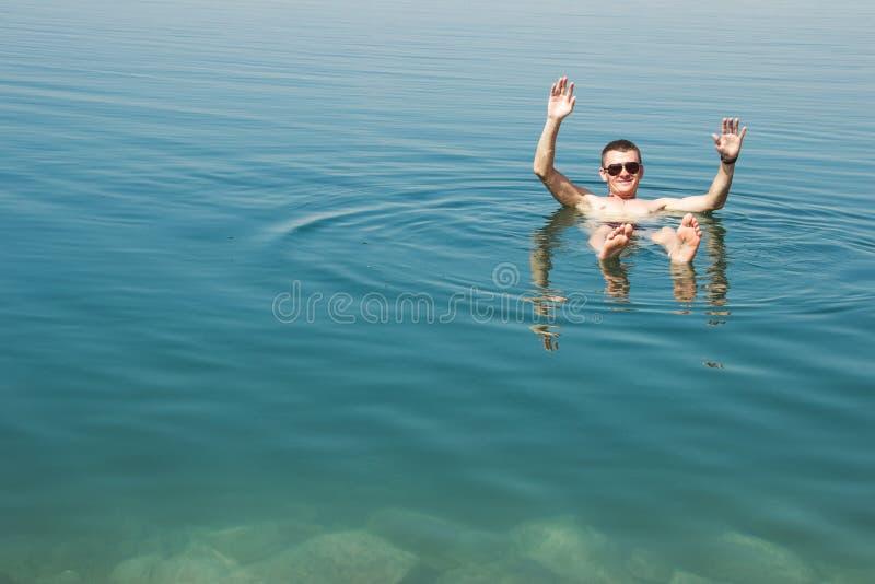 Sirva la mentira en el mar muerto del agua que disfruta de vacaciones en Jordania Reconstrucción del turismo, concepto sano de la foto de archivo libre de regalías