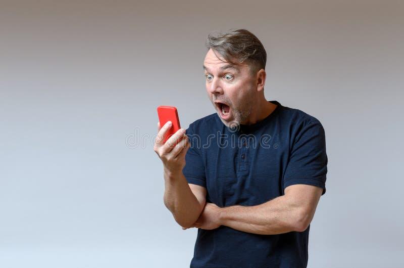 Sirva la mirada de su móvil en choque y horror foto de archivo