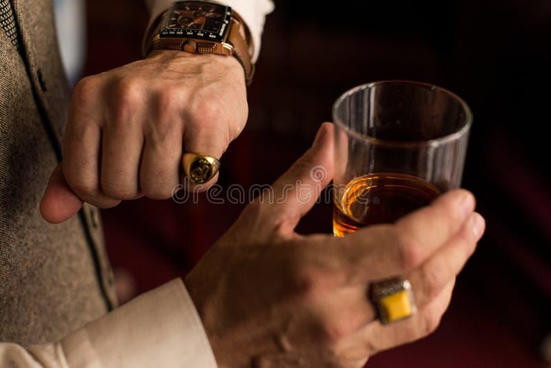 Sirva la mirada de su reloj elegante en la mano izquierda con un anillo en el dedo meñique En mano derecha él que sostiene un vid fotos de archivo