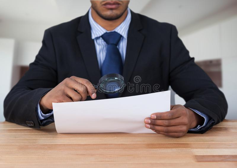 Sirva la mirada del papel con la lupa en el escritorio imagen de archivo