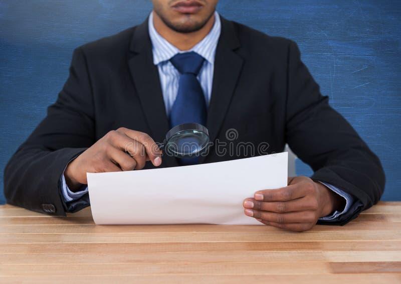Sirva la mirada del papel con la lupa en el escritorio imagenes de archivo
