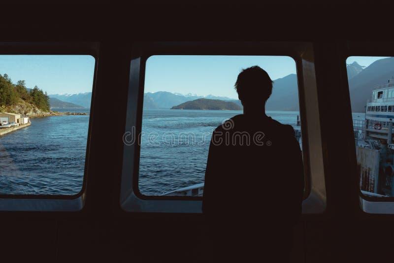 Sirva la mirada a través de ventana en el océano y las montañas fotografía de archivo