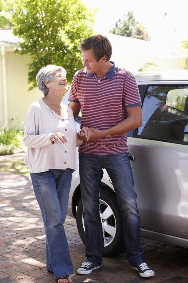 Sirva a la mujer mayor de ayuda en el coche imagenes de archivo