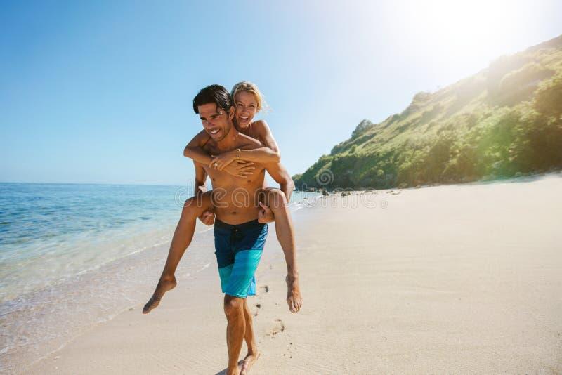 Sirva a la novia que lleva en el suyo detrás a lo largo de la playa fotografía de archivo libre de regalías
