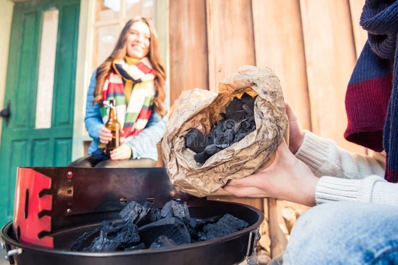Sirva la parrilla de relleno con la mujer sonriente cercana del carbón de leña imagen de archivo