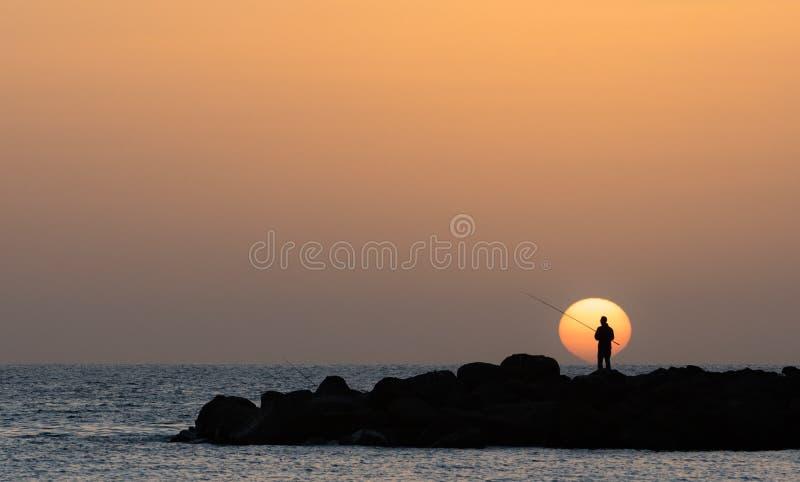 Sirva la pesca, sol bajo en la playa de Amadores en la isla de Gran Canaria en España imagen de archivo libre de regalías