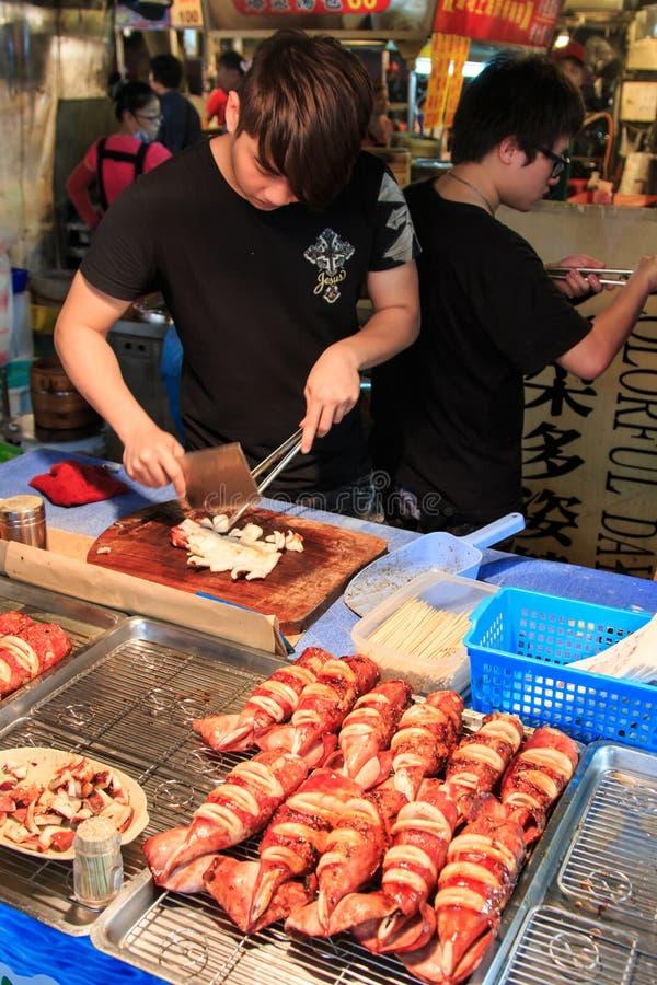 Sirva la preparación del calamar ser vendido en un mercado de la noche de la ciudad de Gaoxiong fotografía de archivo