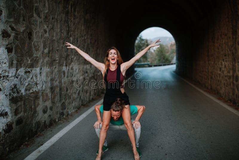 Sirva la preparación llevar a su novia en sus hombros La mujer está aumentando los brazos y la risa emocionados fotografía de archivo