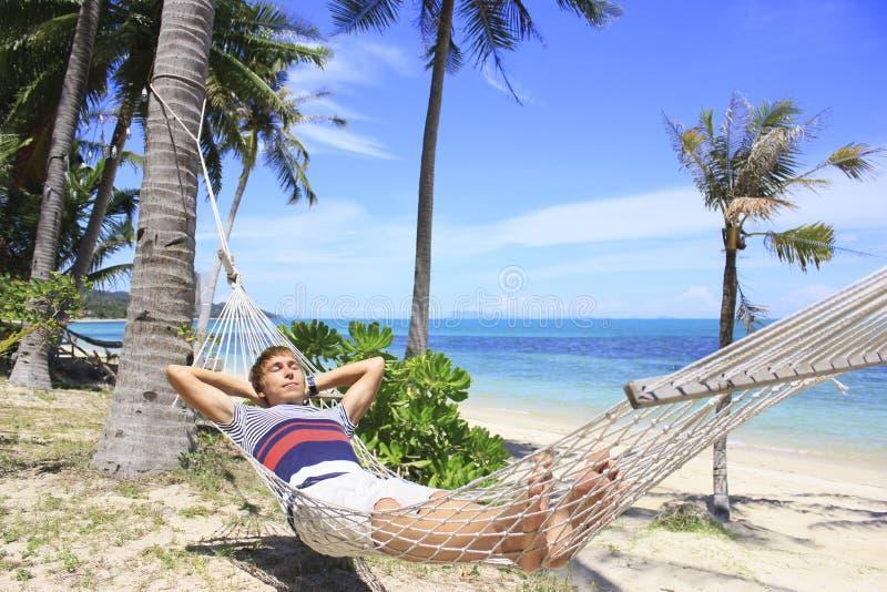 Sirva la reclinación en una hamaca debajo de las palmeras en la playa con el mar blanco de la arena y del azul imagen de archivo
