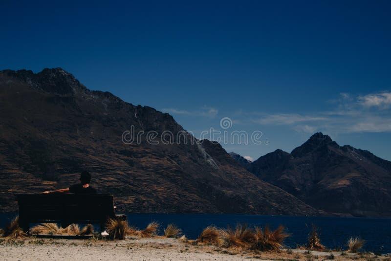 Sirva la reclinación sobre banco cerca del agua y de las montañas fotografía de archivo