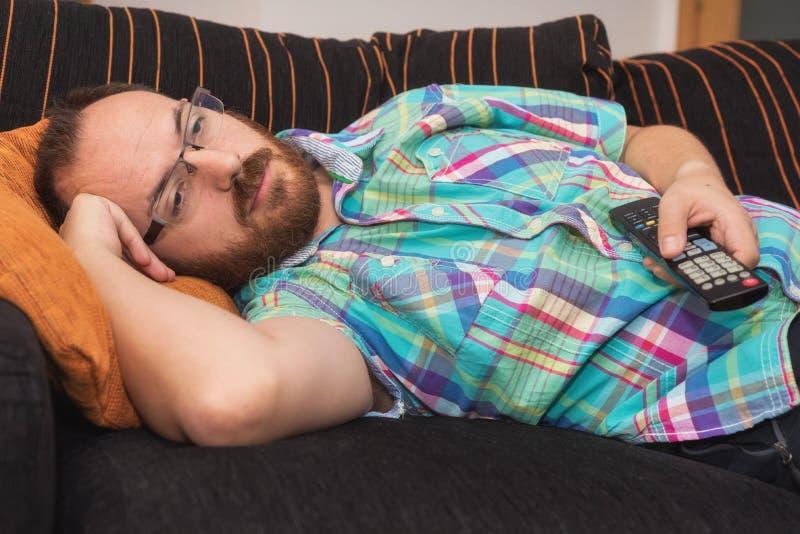 Sirva la relajación en sofá con la TV de observación teledirigida foto de archivo