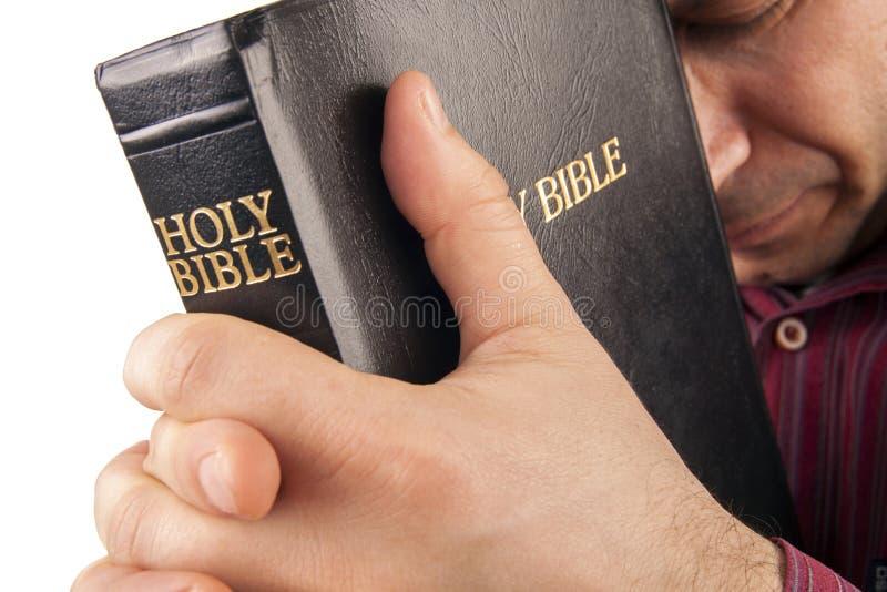 Hombre que ruega sosteniendo la biblia fotografía de archivo libre de regalías