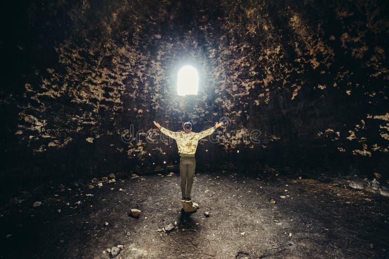 Sirva la rogación y esperar con los brazos aumentados hasta la luz del misterio Concepto del milagro de la religión imagenes de archivo