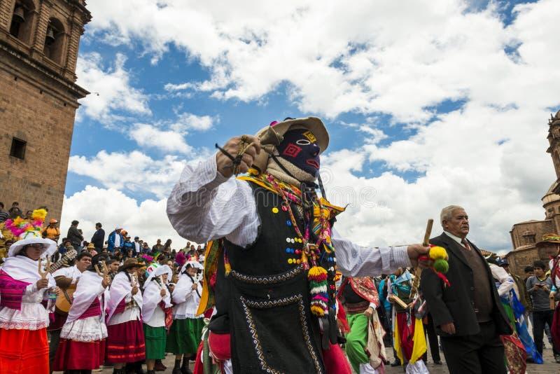 Sirva la ropa y las máscaras tradicionales que llevan que bailan el Huaylia en el día de la Navidad delante de la catedral de Cuz foto de archivo libre de regalías